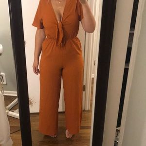 Never worn amber color jumpsuit tie front
